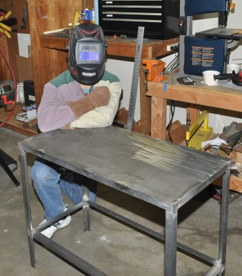 Art posing with his welding table