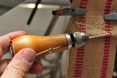 Sewing upholstery webbing with a sewing awl
